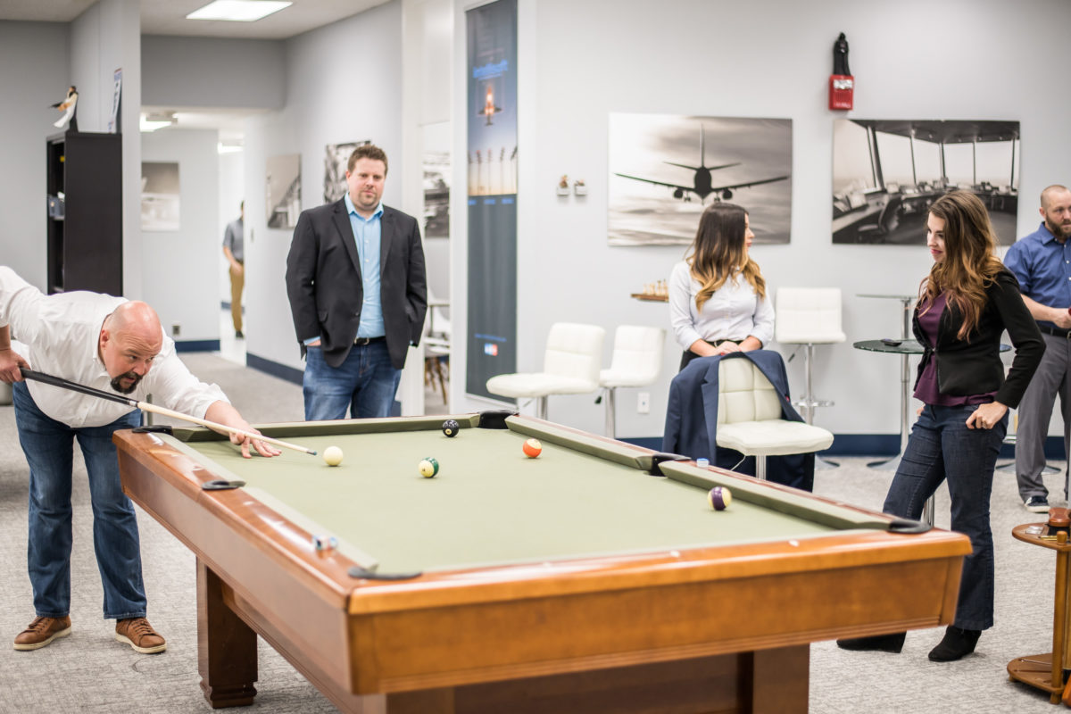 Employees gathering and playing pool